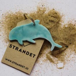 Blå nøglering på sandbaggrund