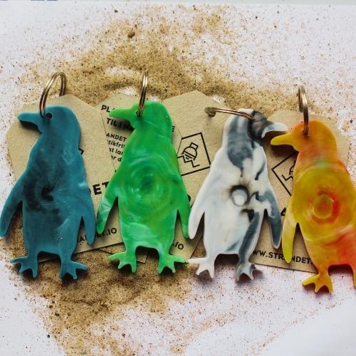 Fire nøgleringe i flotte farver på baggrund af sand