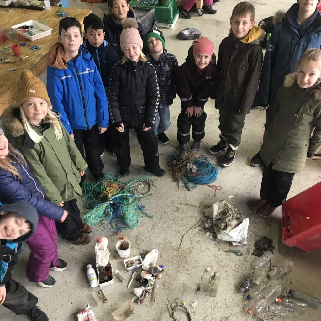 En flok børn står rundt om det affald de har samlet