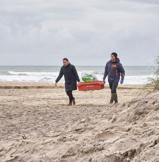 To mennekser går på strand med fiskekasse og andet affald de har opslamet