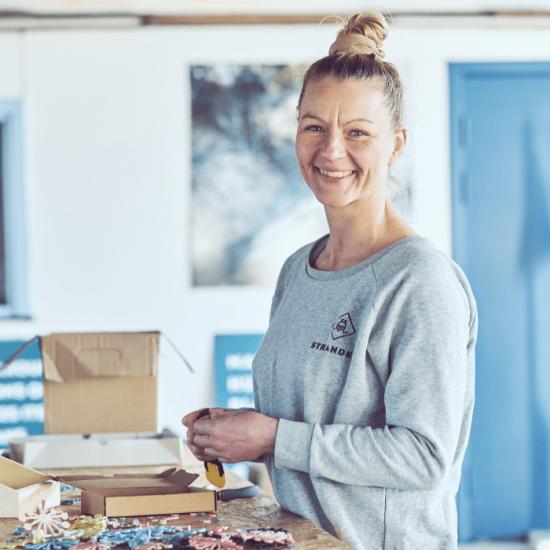 Smilende kvinde i et værksted