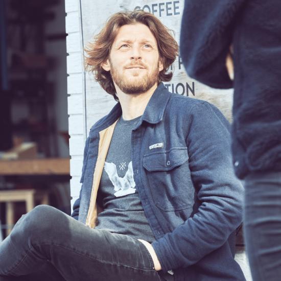 Mand sidder på en bænk og snakker