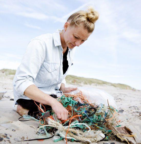 Kvinde samler forskelligt affald på en strand