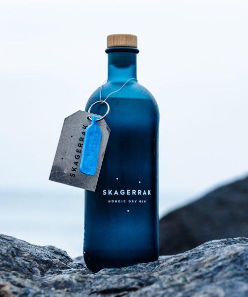 Ginflaske på klippe med havet i baggrunden